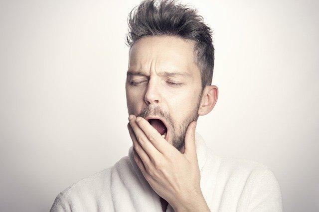Un homme qui baille par manque de sommeil